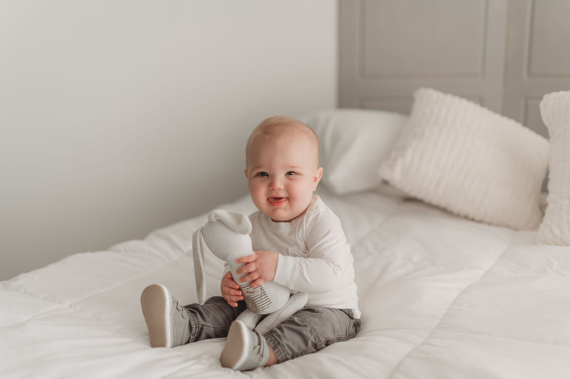 One year old little boy sitting on a bed with white sheets and white pillows, wearing a white shirt, gray pants, and gray shoes, smiling, and holding a stuffed bunny