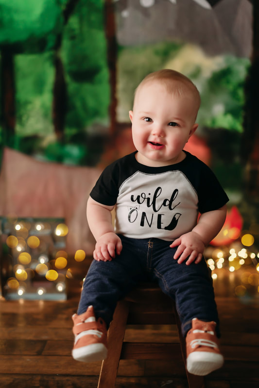 "One year old little boy wearing jeans, a white and black shirt that writes ""wild one"", with blurred out lights and a forest background"