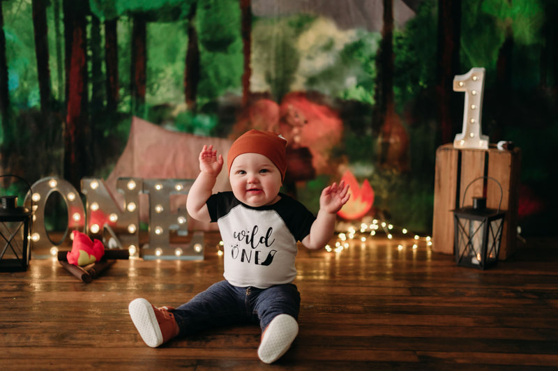 "One year old little boy wearing jeans, a white and black shirt that writes ""wild one"", a fox hat, fox shoes, with blurred out lights and a forest background"