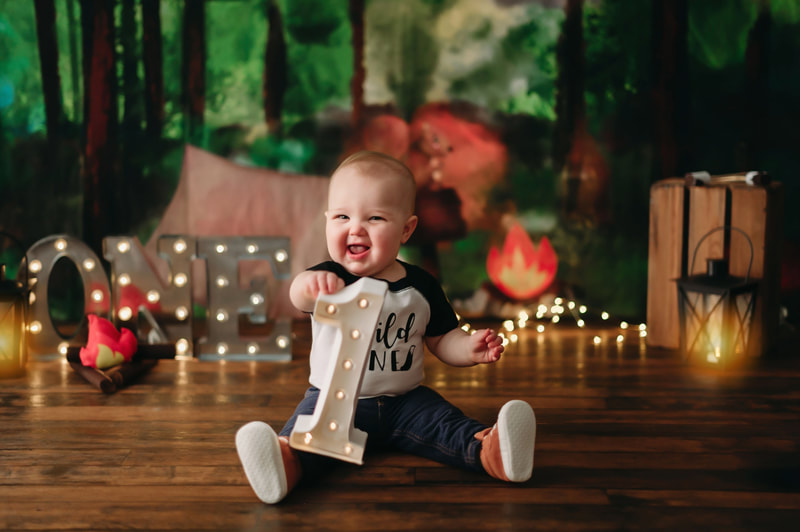 "One year old little boy holding a lite up number one, wearing jeans, a white and black shirt that writes ""wild one"", with blurred out lights and a forest background"