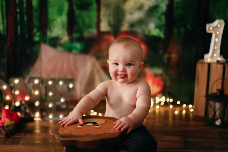 One year old little boy wearing jeans, with blurred out lights and a forest background. He is playing on a stole that has a bears face on it.