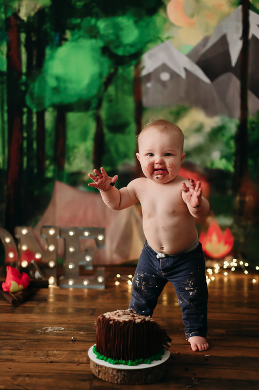 One year old little boy wearing jeans, with blurred out lights and a forest background. He has cake all over his face, hands, and pants.