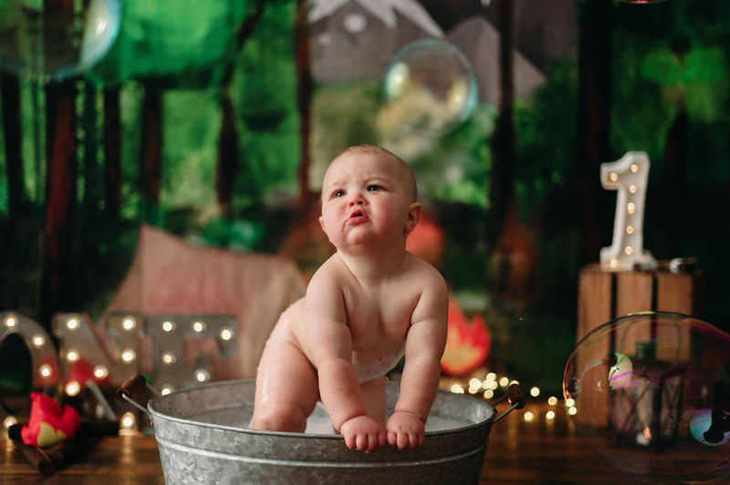 One year old little boy naked in a small bucket tub taking a bath, with blurred out lights and a forest background.