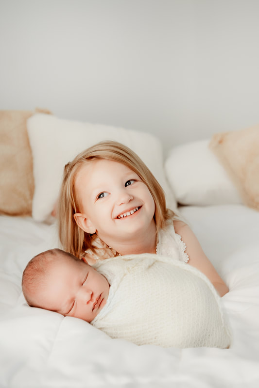 baby boy on a white bed with his older sister swaddled in a cream blanket while sister holds him
