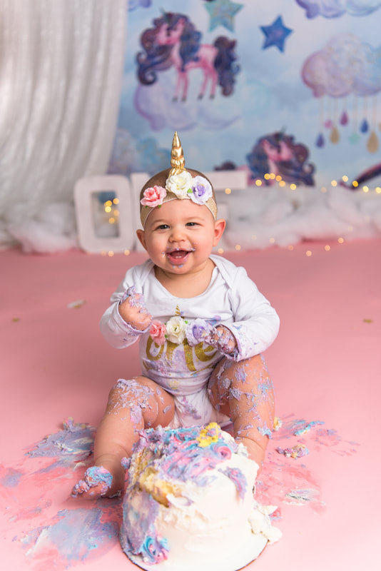 Baby in unicorn headband covered in cake