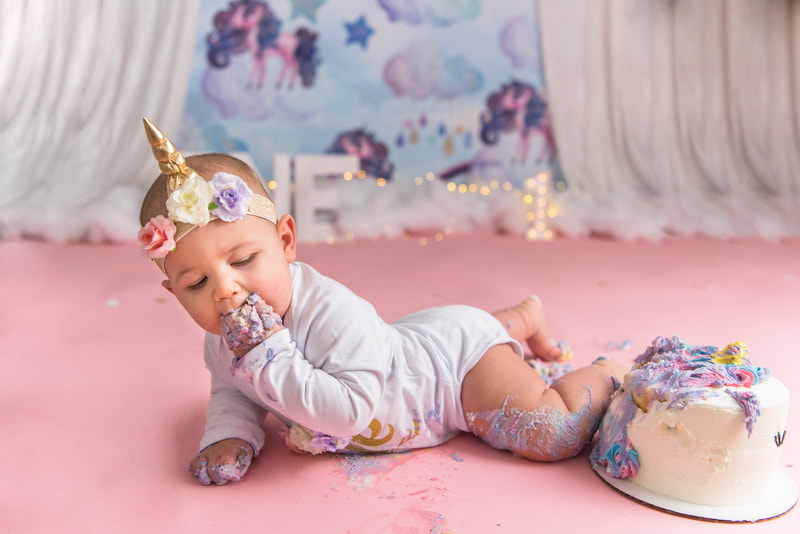Baby laying on her stomach eating unicorn cake