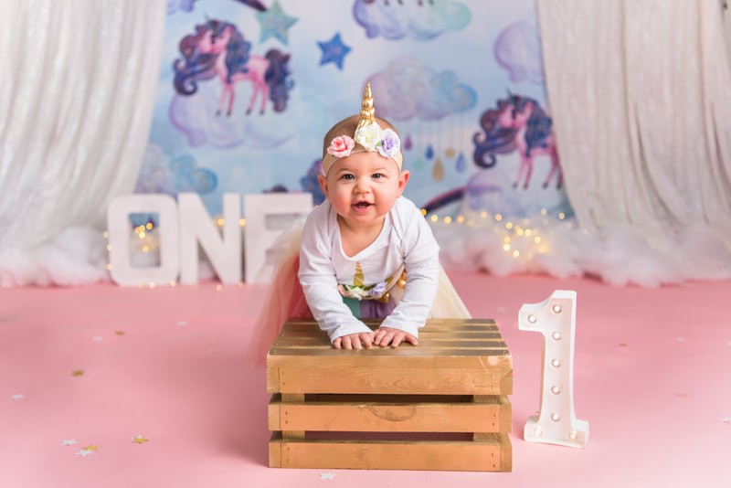 Baby posing for unicorn first birthday photos