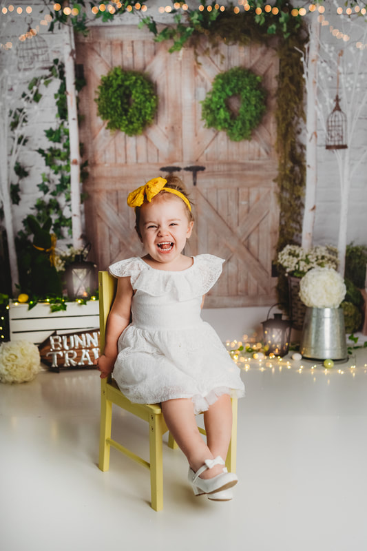 2 year old girl sitting on a small yellow chair in white dress and yellow headband.