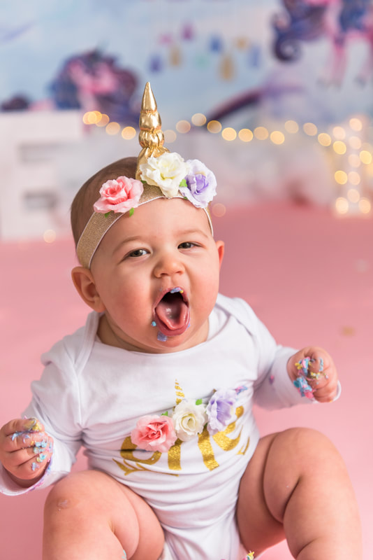 Baby sticking out tongue covered in cake
