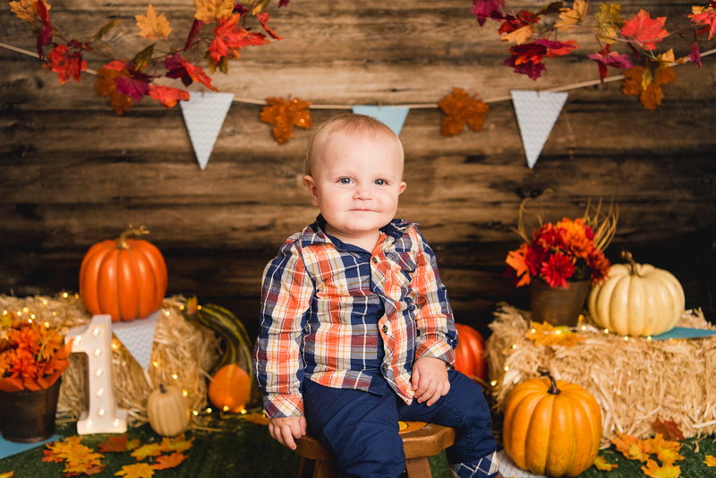 Boy in fall set up with pumpkins for first birthday cake smash