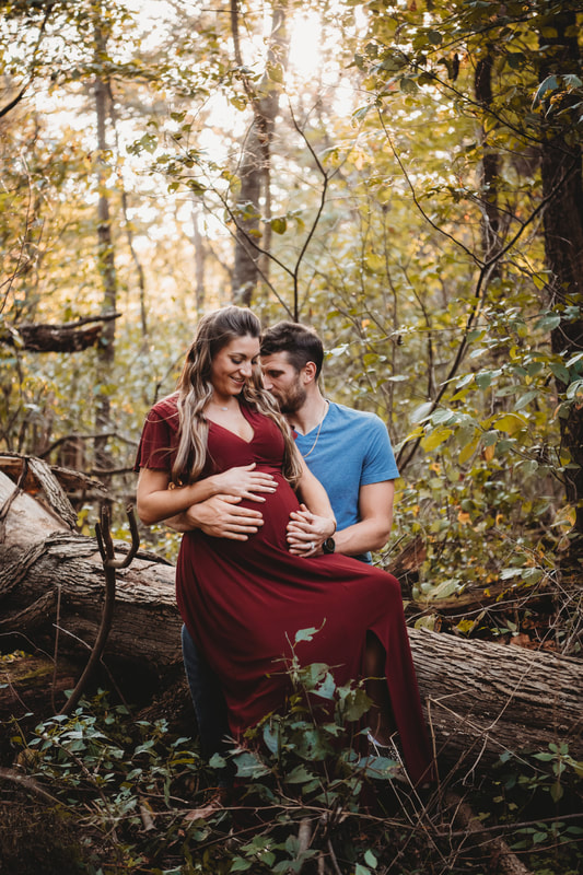 Maternity session couple sitting on a log in townsend park