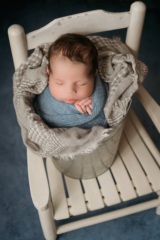 sleeping baby boy in a silver bucket on a white chair swaddled in a blue blanket