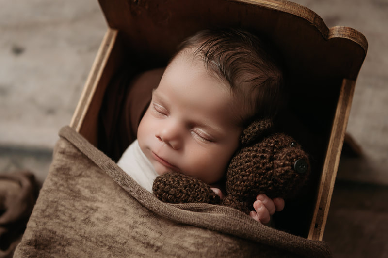 sleeping baby boy in a brown bed holding a dark brown stuffed bear tucked in with a brown blanket