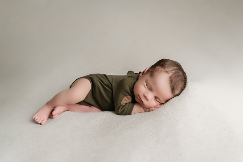 sleeping baby boy on a tan blanket wearing a green onesie with tan elbow patches