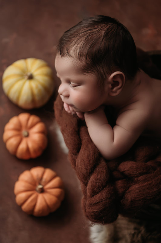 baby boy sleeping on a brown fluffy blanket surrounded by pumpkins