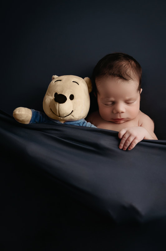 Sleeping baby boy tucked in with a dark blue blanket cuddling a stuffed Winnie the Pooh plush